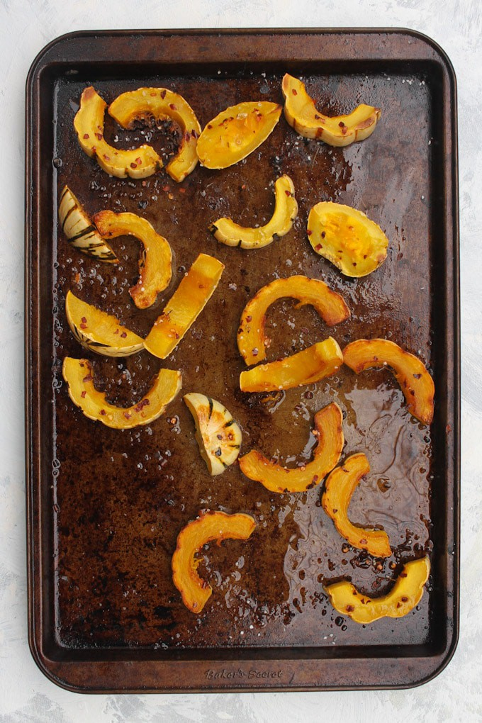 delicata squash slices on a baking tray