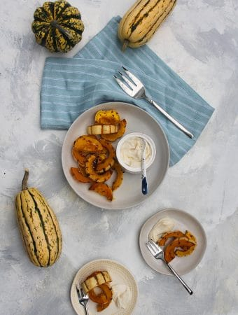 roasted delicata squash in a serving bowl with tahini yogurt sauce on the side