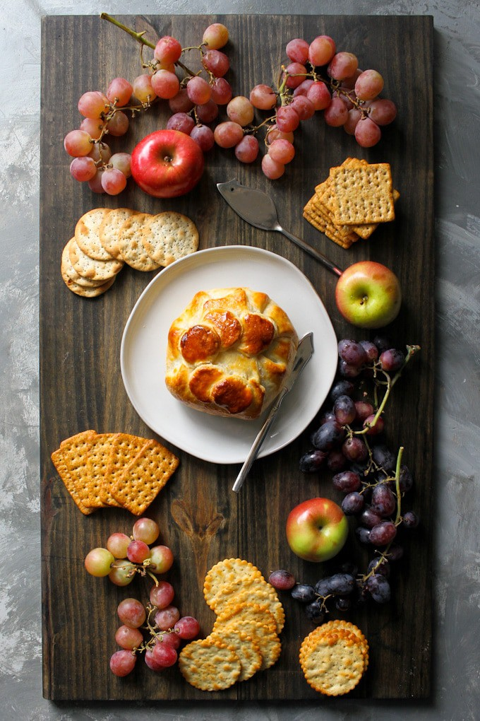 Baked brie in puff pastry on a cheese board with fruit and crackers