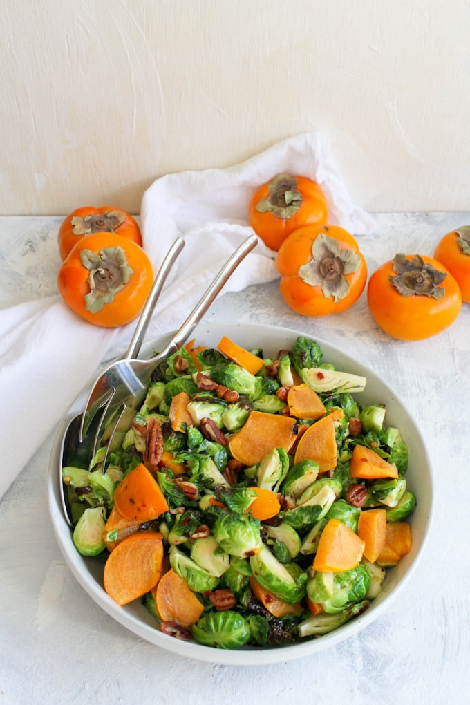 roasted brussels sprouts salad with persimmon in a serving dish