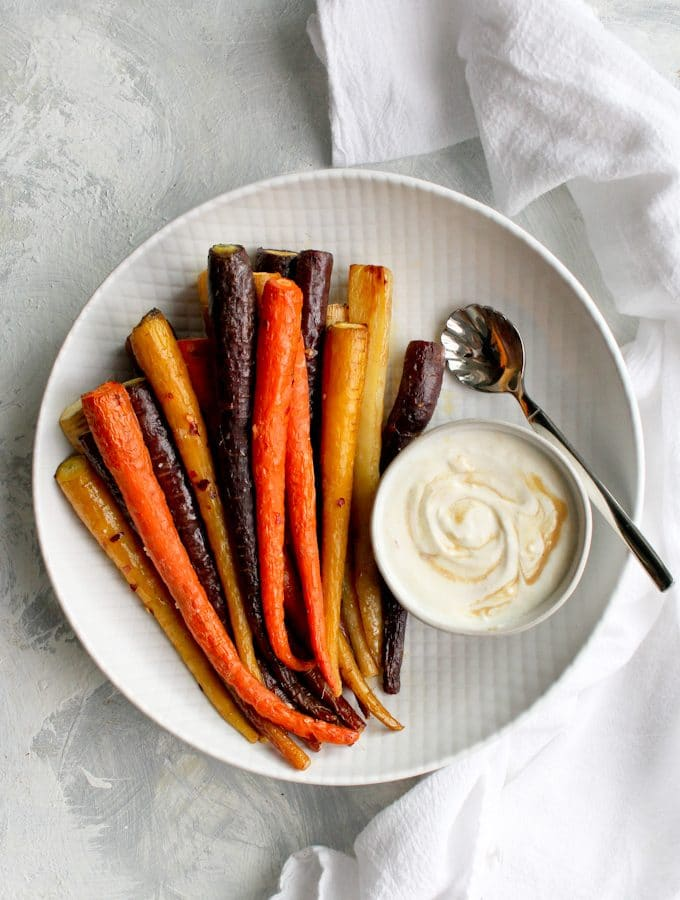 whole roasted carrots on a serving tray with tahini sauce