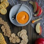 roasted red pepper dip on a serving tray with crackers and apples