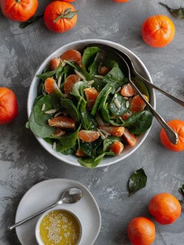 spinach mandarin orange salad in a serving dish