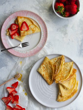 french crepe recipe: basic crepes on a serving dish with strawberries