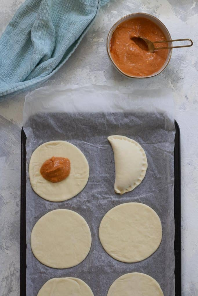 Add pumpkin filling to the dough, and seal empanada