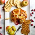 This easy cranberry baked Brie is made with flaky, golden puff pastry, cranberry sauce, chopped nuts, and a wheel of Brie. It's the perfect centerpiece for a winter cheeseboard at your next party!