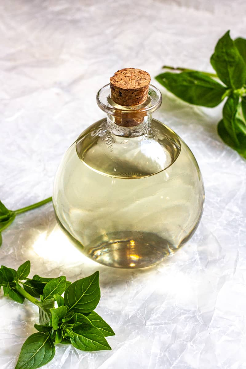 basil simple syrup in a glass bottle