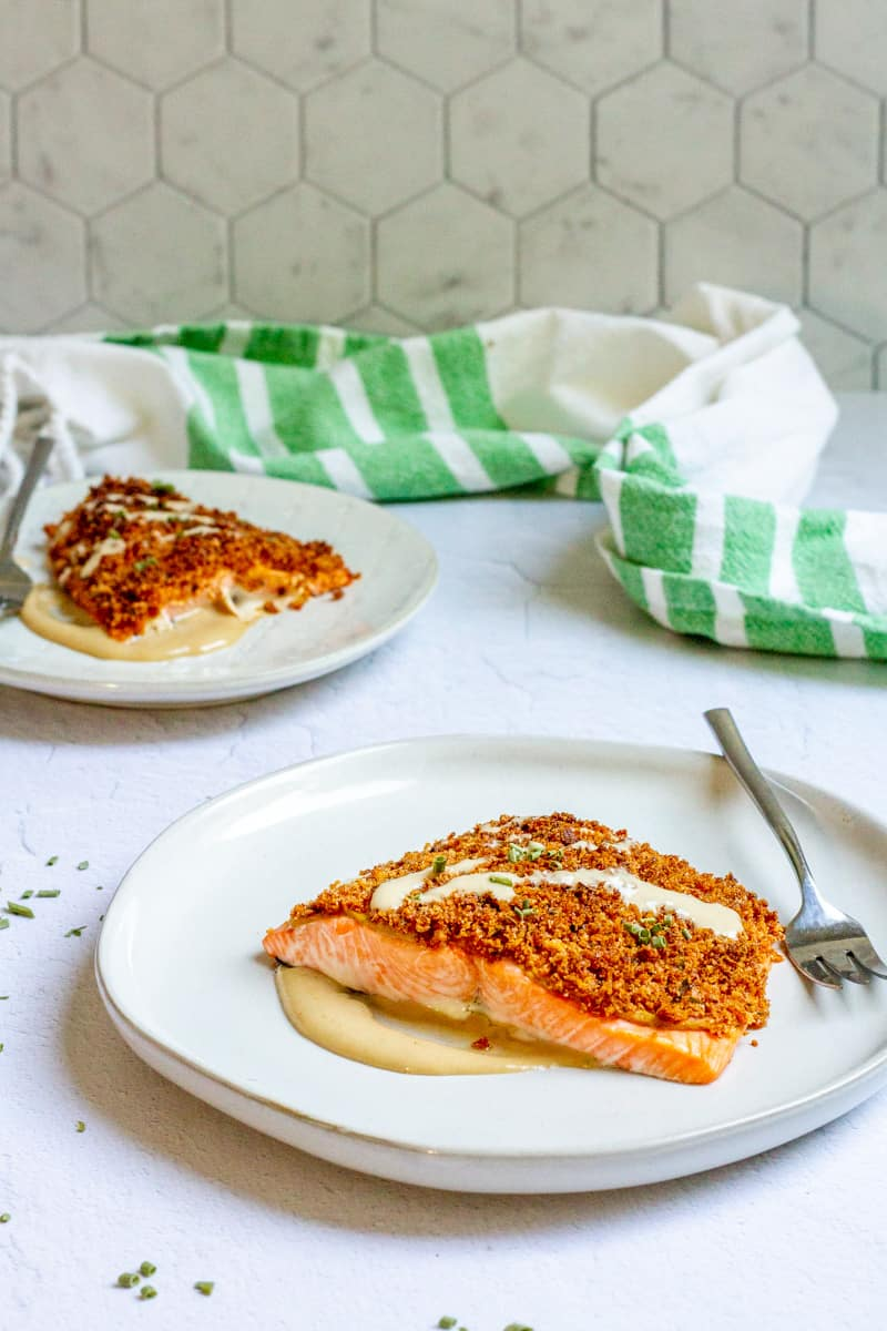 Baked mustard salmon on a plate with tahini dressing