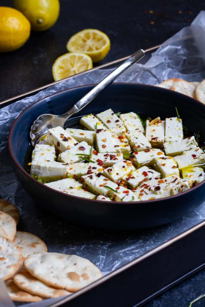 Marinated feta in a bowl on a serving tray with crackers