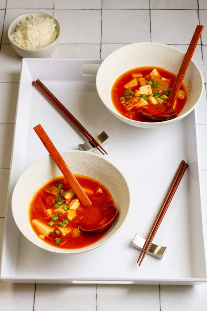 Vegan kimchi soup in bowls on a serving tray
