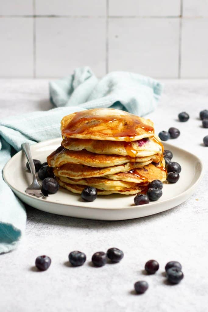 sourdough blueberry pancakes stacked on a plate with syrup and extra berries