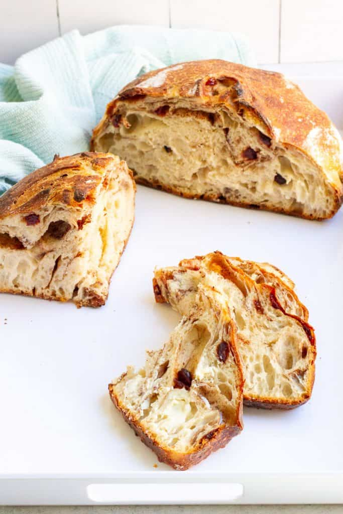 cinnamon sourdough bread with cranberries or raisins on a serving platter, partially cut into slices