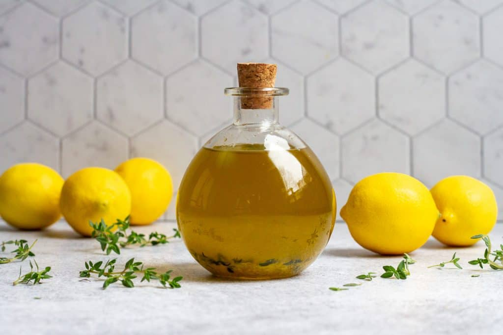 lemon olive oil in a glass bottle with lemons and herbs around the bottle