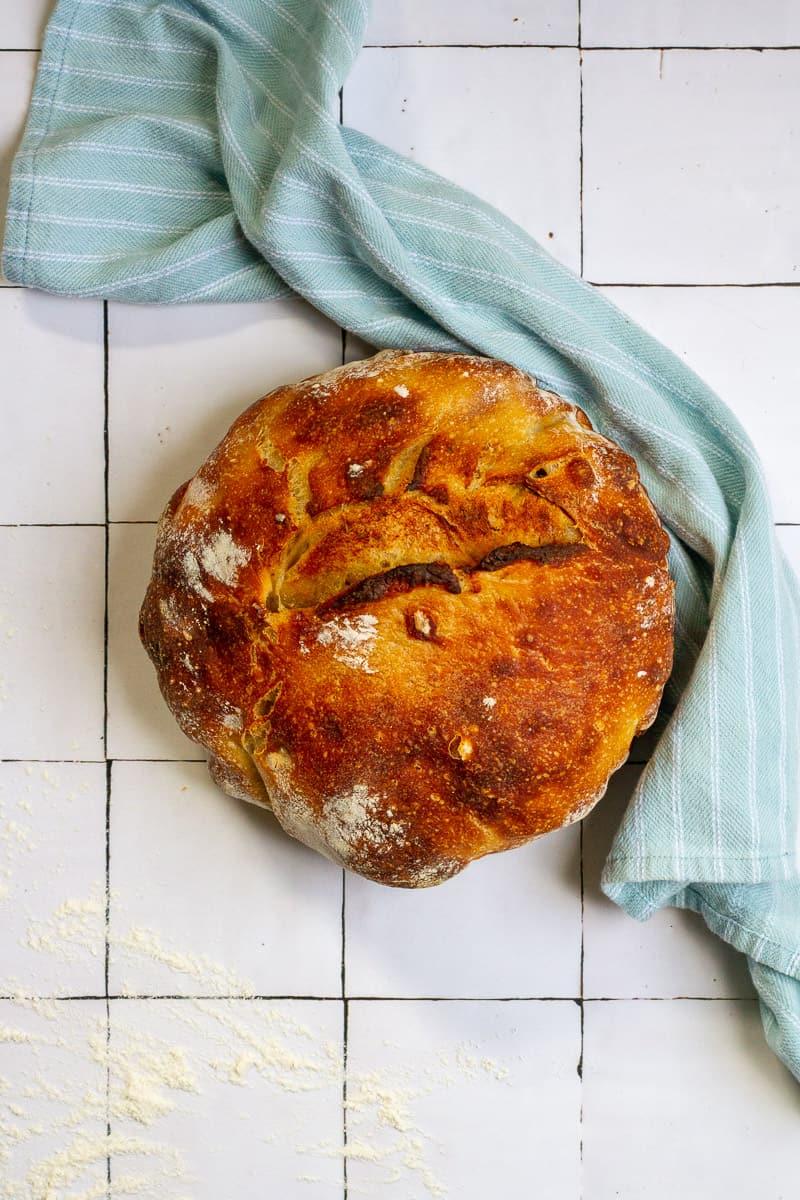 rosemary garlic sourdough bread on a tile countertop with a towel