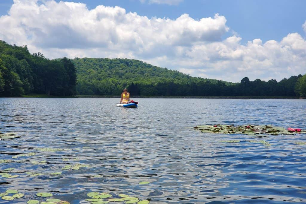 Person paddling on board in middle of lake