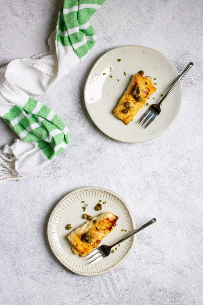 Haddock with lemon caper sauce on plates