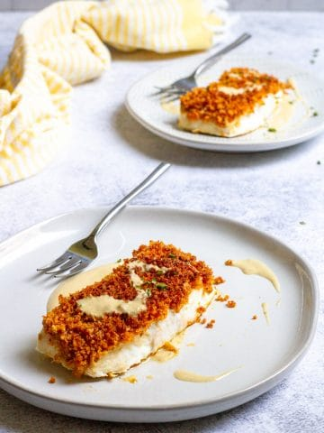 panko crusted halibut on plates with tahini sauce