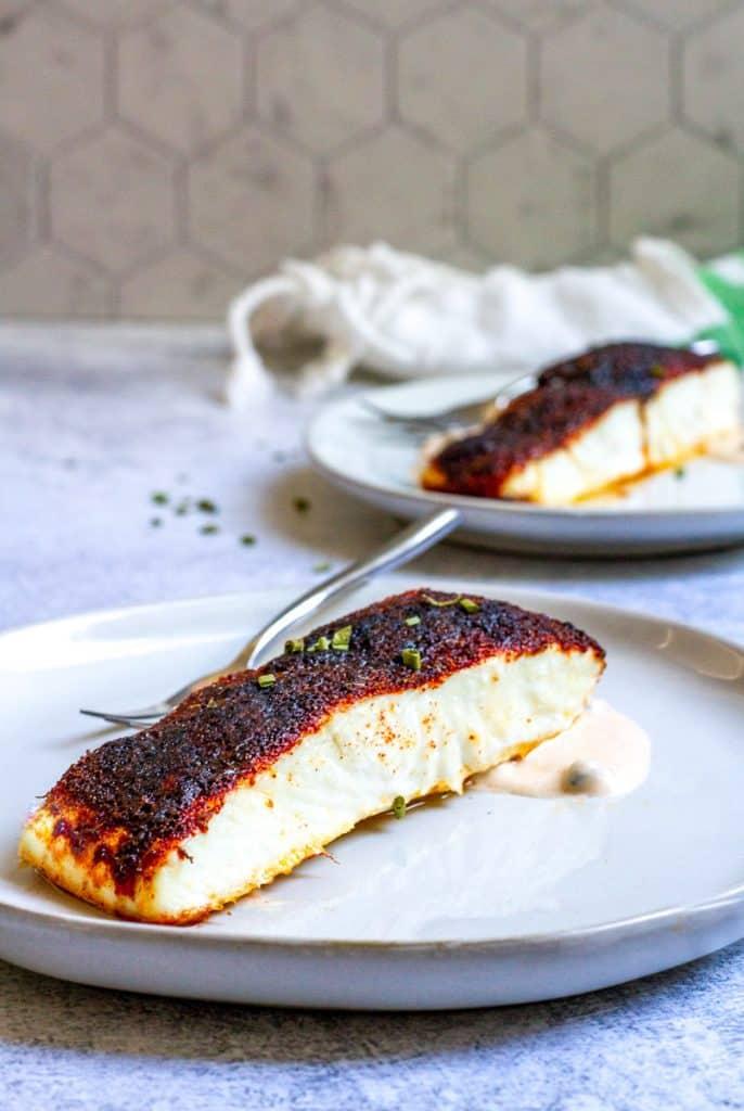 blackened halibut with spicy yogurt sauce on plates.
