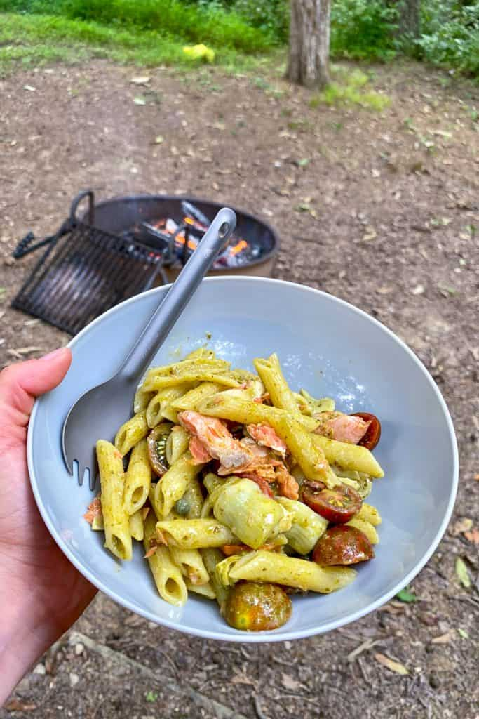 Finished camping pasta recipe of pesto penne with smoked salmon in a bowl.