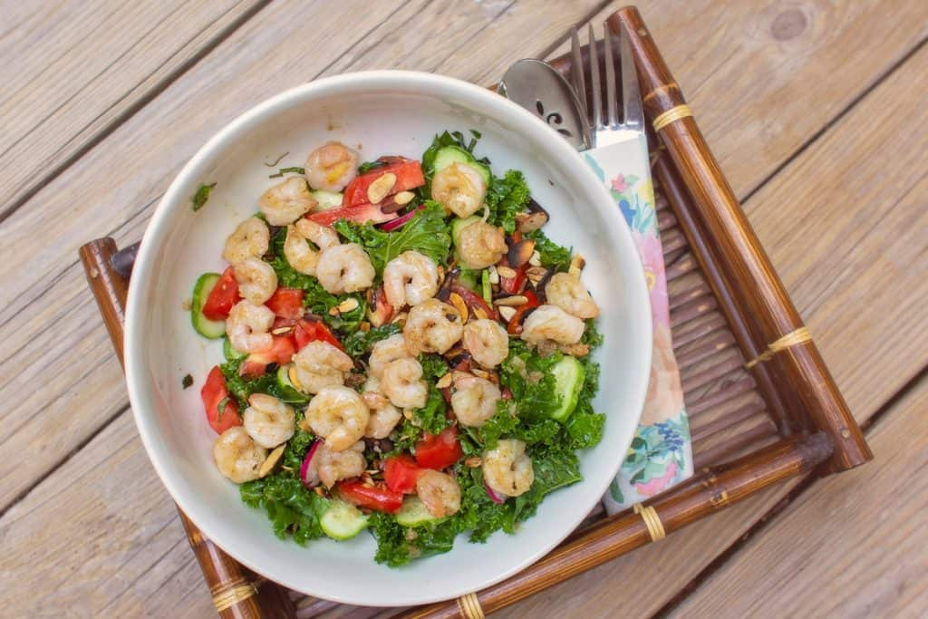Grilled shrimp and toasted almond salad with kale, tomatoes, fennel, cucumber, radish, and green onion