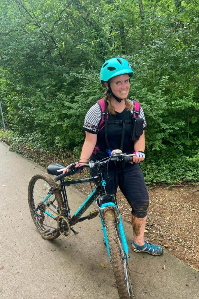 Standing with a Muddy Mountain Bike