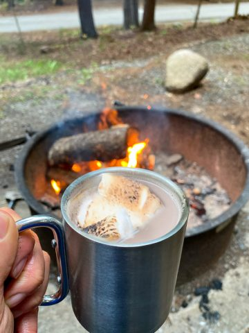 Campfire hot chocolate with peanut butter whiskey and toasted marshmallows in front of a campfire.