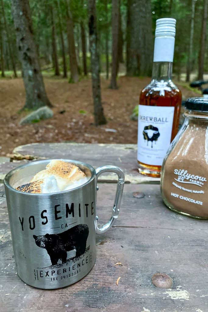 Hot chocolate in a mug with hot chocolate mix + peanut butter whiskey in the background.
